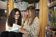 Two young women having fun in the library - IGGF00567
