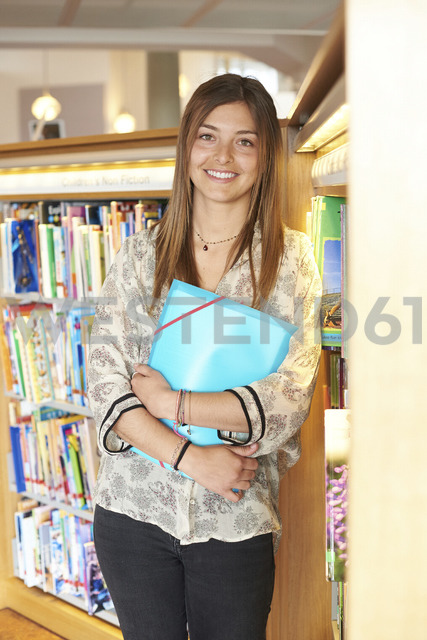 Portrait of smiling young woman with folder leaning against bookshelf in the library - IGGF00573