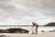 Young woman at the beach preparing surfboard - UUF15031