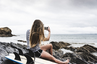 Young woman with surfboard sitting on the beach, using smartphone - UUF15040