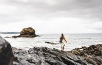 Young woman carrying surfboard on a rocky beach at the sea - UUF15043
