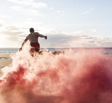 Man doing movement training at the beach with red smoke - UUF15052