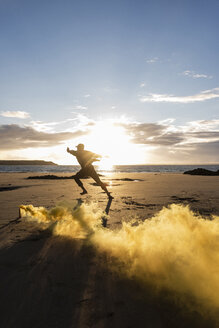 Man doing movement training at the beach with colorful smoke at sunset - UUF15055