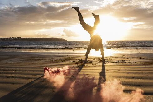 Man doing movement training at the beach with colorful smoke at sunset - UUF15064
