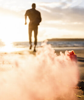 Young man running on the beach at sunset with colorful smoke - UUF15067