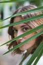 Young woman looking through palm leaf, portrait - KKAF01665