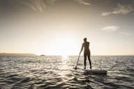 Young woman stand up paddle surfing at sunset - UUF15072