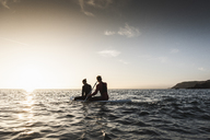 Couple on paddling on paddleboard at sunset on the sea - UUF15078