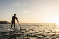 Young man on paddleboard at sunset - UUF15084