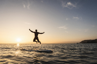 Young man jumping from paddleboard into water at sunset - UUF15090