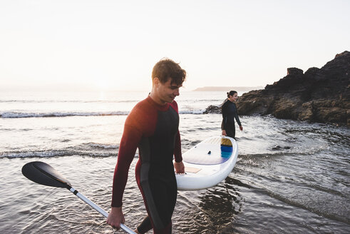 Couple carrying paddleboard - UUF15093