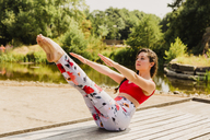 Young woman practicing Pilates in an urban park - NMSF00226