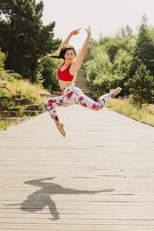 Young woman practicing Pilates in an urban park - NMSF00232
