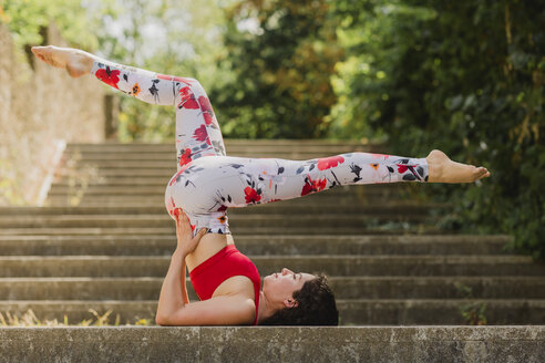 Young woman practicing Pilates in an urban park - NMSF00244