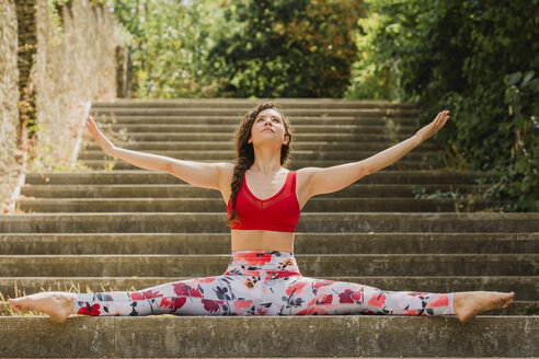 Young woman practicing Pilates in an urban park, spagat on steps - NMSF00247
