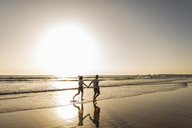 Young couple doing a romantic beach stroll at sunset - UUF15098