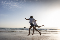 Young couple having fun on the beach, running and jumping at the sea - UUF15107