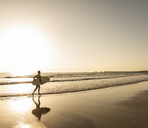 Young man running on beach, carrying surfboard - UUF15113