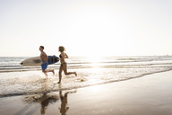 Young couple running on beach, carrying surfboard - UUF15122