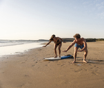 Young man showing young woman how to surf on the beach - UUF15128