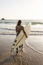Young woman walking in water, carrying surfboard - UUF15131