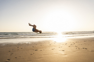 Young man doing somersaults on the beach - UUF15134