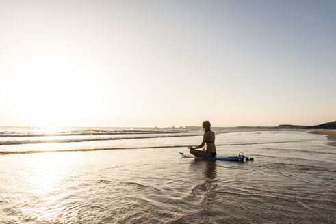 Young woman practicing yoga on the beach, sitting on surfboard, meditating - UUF15137