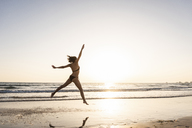 Young woman jumping for joy on the beach - UUF15143
