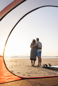 Romantic couple camping on the beach, embracing at sunset - UUF15146