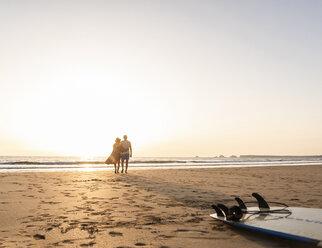 Romantic couple doing a beach stroll at sunset - UUF15149