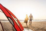 Romantic couple camping on the beach, doing a beach stroll at sunset - UUF15152