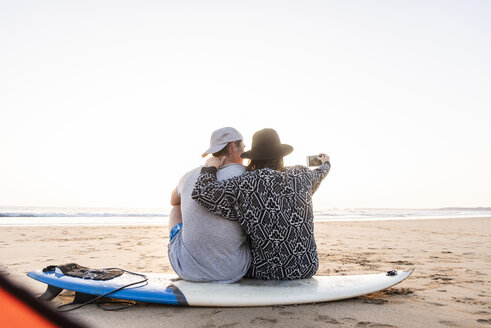 Couple camping on the beach, taking smartphone selfies - UUF15155
