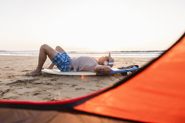 Young surfer relaxing on the beach, listening music - UUF15158