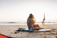 Young woman sitting on surfboard, taking pictures of young man, practicing handstands on the beach - UUF15161