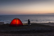 Young woman sitting by tent, looking at the sea at night - UUF15167