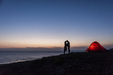 Romantic couple camping on the beach, kissing in twilight - UUF15170