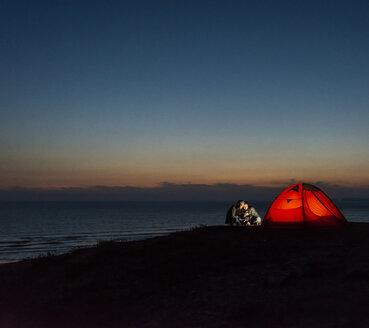 Romantic couple camping on the beach, using smartphone - UUF15173