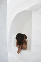 Young woman crouching in a wall niche - IGGF00578