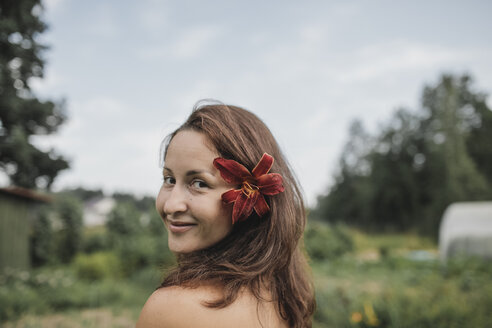 Portrait of smiling woman with flower in her hair - KMKF00547