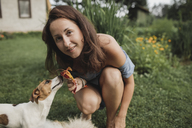 Portrait of smiling woman with Jack Russel Terrier in garden - KMKF00550