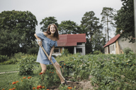 Portrait of happy woman working in garden - KMKF00553