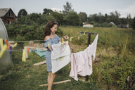 Woman hanging up laundry in garden - KMKF00556