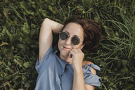 Portrait of smiling woman wearing sunglasses lying in grass with flower in her mouth - KMKF00571