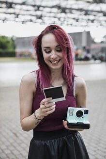 Happy young woman with instant camera and photo outdoors - MAUF01693
