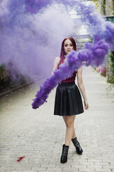 Young woman holding smoke torch outdoors - MAUF01702