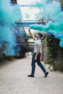 Young man walking with smoke torch outdoors - MAUF01705