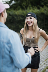Young woman laughing at man outdoors - MAUF01714