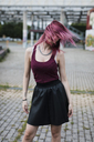 Young woman shaking her dyed hair outdoors - MAUF01717