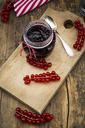 Jam jar of currant jelly and red currants on wooden board - LVF07414