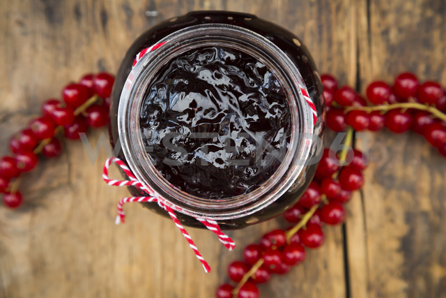 Jam jar of currant jelly and red currants on wood - LVF07417